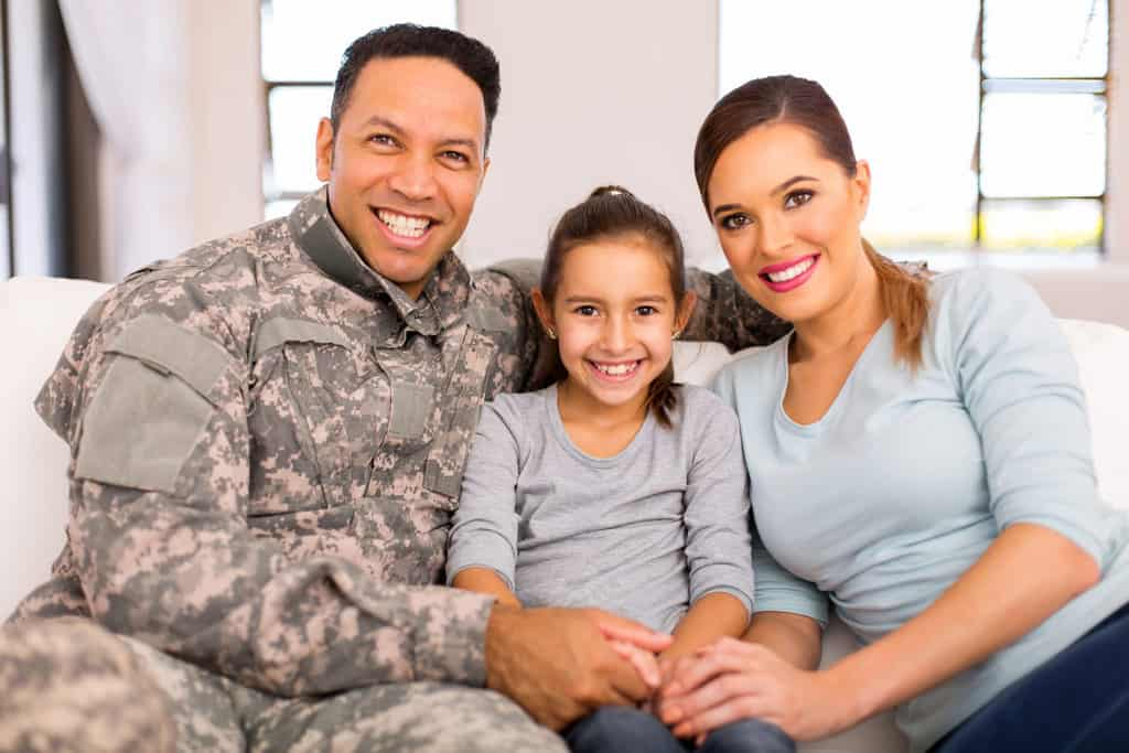 Young military family sitting on couch