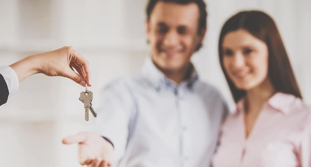 Close up. Realtor Giving House Keys to Smiling Couple. Real Estate Sales Concept. Getting Access to Home Concepts. Investment and Buying Property Concepts. Real Estate Realtor Work.